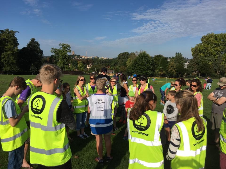 Volunteers in high vis jackets being briefed ready to help at a parkrun